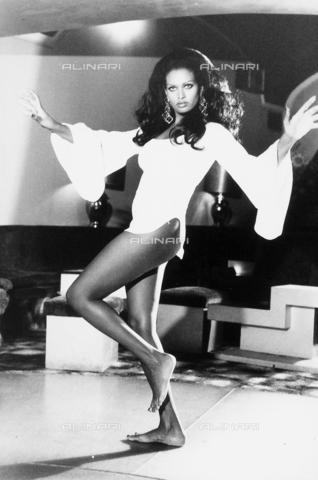 TEA-S-000032-0006 - Ritratto di Zeudi Araia in un interno di appartamento. L'attrice, in piedi, davanti ad un salottino, indossa solo una maglietta a maniche ampie - Data dello scatto: 1970 - 1980 - Archivi Alinari, Firenze