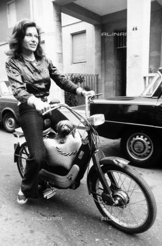 """TEA-S-000135-0005 - L'attrice Erika Blanc in sella a un motorino """"Ciao"""" della Piaggio, trasporta il suo cane di razza Yorkshire terrier dentro una borsa di paglia - Data dello scatto: 1970 - 1975 - Archivi Alinari, Firenze"""