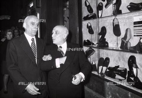 TEA-S-000193-0001 - Amintore Fanfani e Campilli fotografi a passeggio nel centro di Roma. Alla loro sinistra la vetrina di un negozio di scarpe - Data dello scatto: 1970-1980 - Archivi Alinari, Firenze