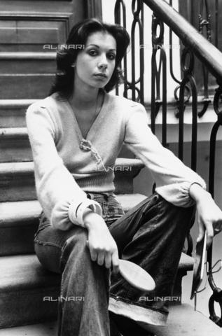 TEA-S-000248-0001 - Ritratto di Sonia Ciuffi vestita con jeans, seduta sul gradino di una scala. Tiene in una mano una spazzola e nell'altra uno specchio - Data dello scatto: 1970-1979 - Archivi Alinari, Firenze