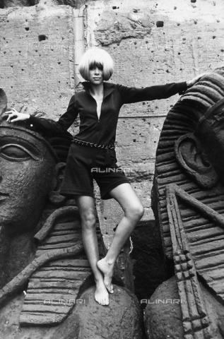 TEA-S-000291-0006 - Ritratto dell'attrice Mireille Darc, in piedi tra due sculture che rappresentano teste di faraone. - Data dello scatto: 1970-1980 - Archivi Alinari, Firenze