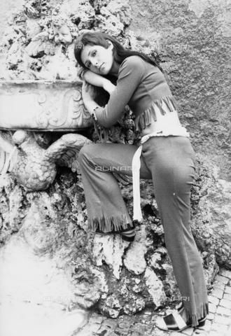 TEA-S-000366-0001 - Ritratto della modella Fiammetta appoggiata ad una fontana. Indossa un completo con pantaloni a frange. - Data dello scatto: 1970 - 1979 ca. - Archivi Alinari, Firenze