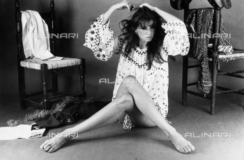 TEA-S-000447-0001 - L'attrice Angelica Ippolito seduta sul pavimento mentre si tocca i capelli. Accanto a lei due sedie con alcuni indumenti. - Data dello scatto: 1970 - 1980 - Archivi Alinari, Firenze
