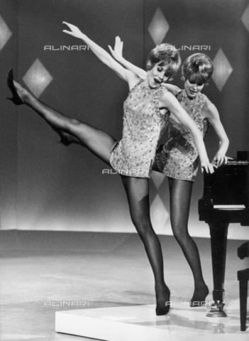 TEA-S-000459-0001 - Alice ed Ellen Kessler fotografate durante un balletto di una trasmissione televisiva. Sulla destra si vede parte di un pianoforte, al quale le famose sorelle si appoggiano per un passo di danza - Data dello scatto: 1965-1970 ca. - Archivi Alinari, Firenze