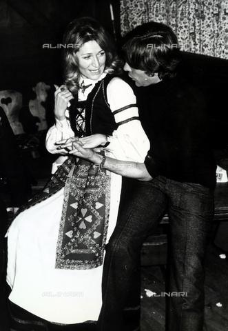 TEA-S-000544-0002 - La stilista Marta Marzotto, in costume folkloristico, conversa con un giovane uomo in un interno - Data dello scatto: 1970 -1975 ca. - Archivi Alinari, Firenze