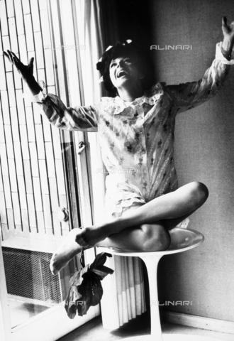 TEA-S-000568-0011 - L'attrice Sandra Milo, seduta a gambe incrociate su di uno sgabello, con la testa e le braccia rivolte verso l'alto. Attaccato ad un piede un grande fiore di carta. - Data dello scatto: 1965-1975 ca. - Archivi Alinari, Firenze