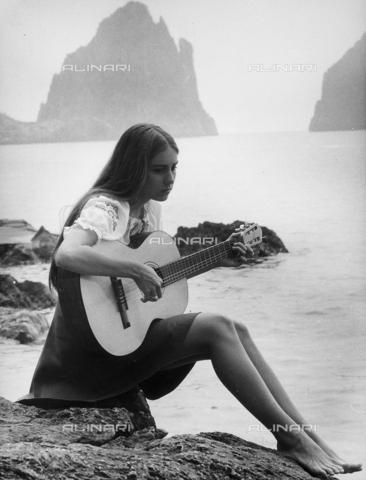 TEA-S-000668-0011 - Ritratto dell'attrice e cantante Romina Power, seduta su uno scoglio in riva al mare, nell'atto di suonare la chitarra. - Data dello scatto: 1970 ca. - Archivi Alinari, Firenze