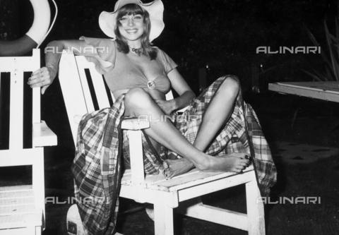 TEA-S-000859-0003 - Ritratto dell'attrice Sylva Winter che sorride seduta a gambe incrociate, con un'ampia gonna a quadri, su una sedia di legno - Data dello scatto: 1970 - 1980 - Archivi Alinari, Firenze