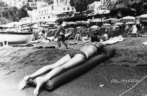 TEA-S-000938-0013 - Primo piano di una donna distesa su un materassino gonfiabile sulla spiaggia di Positano - Data dello scatto: 1970 - 1980 - Archivi Alinari, Firenze