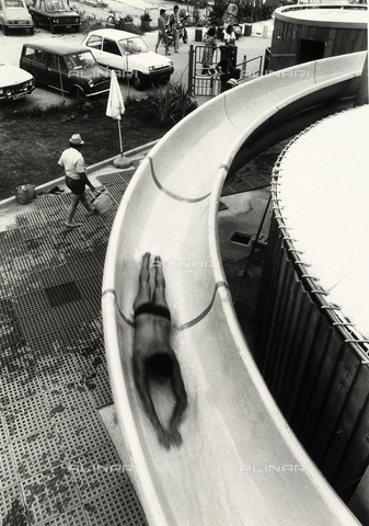 TEA-S-000938-0014 - A man quickly sliding down a tube in a swimming pool. In the background a parking lot with cars and people at the entrance gate are visible