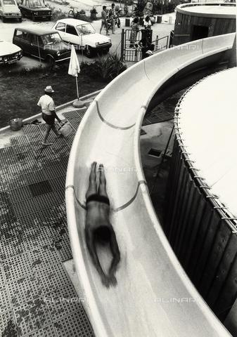 TEA-S-000938-0014 - Un uomo disteso scorre, veloce, sulla curva dello scivolo di una piscina. Sullo sfondo un parcheggio con auto e alcune persone al cancello d'ingresso