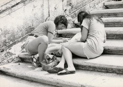 TEA-S-000953-0001 - Due giovani turiste scrivono cartoline appoggiate ad una scalinata - Data dello scatto: 1970-1979 - Archivi Alinari, Firenze