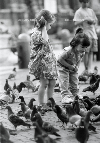 TEA-S-000971-0003 - Two little girls surrounded by numerous pigeons in a square