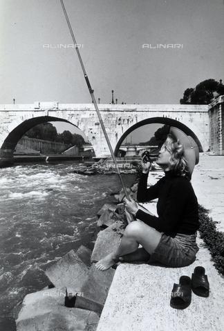TEA-S-000972-0005 - Donna con pipa e cappello pesca sull'Isola Tiberina a Roma - Data dello scatto: 1970 ca. - Archivi Alinari, Firenze