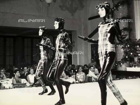 TEA-S-001047-0007 - Sfilata di moda a Capri. Tre modelle sfilano in passerella con tute-alternative e copricapi in materiale lucido. Sullo sfondo è visibile il pubblico che assiste alla sfilata. - Data dello scatto: 1968 - Archivi Alinari, Firenze