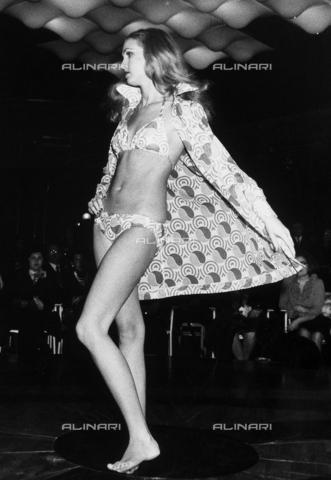 TEA-S-001055-0001 - Sfilata di moda. Una modella indossa un costume da bagno a due pezzi, con copricostume in tessuto fantasia, firmato dalla stilista Cleonice Capece. Sullo sfondo è visibile il pubblico che assiste alla sfilata. - Data dello scatto: 1972 - Archivi Alinari, Firenze