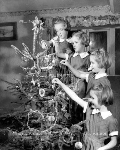 TOP-F-022482-0000 - Bambine che appendono decorazioni sull'albero di Natale. 23 Dicembre 1955, Generale - Data dello scatto: 23/12/1955 - 2005 / TopFoto / Archivi Alinari