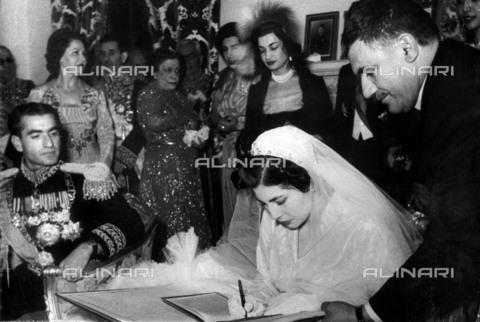 TOP-F-025907-0000 - Lo scià di Persia e la sua sposa, Soraya Esfandayiari, durante la cerimonia di nozze nel palazzo di marmo a Teheran. Soraya indossò un abito color argento e blu ghiaccio, scintillante di 6000 diamanti e del valore di 1 500 000. 14 Febbraio 1951, Reali, Matrimonio scià di Persia - Data dello scatto: 14/02/1951 - 2005 / TopFoto / Archivi Alinari