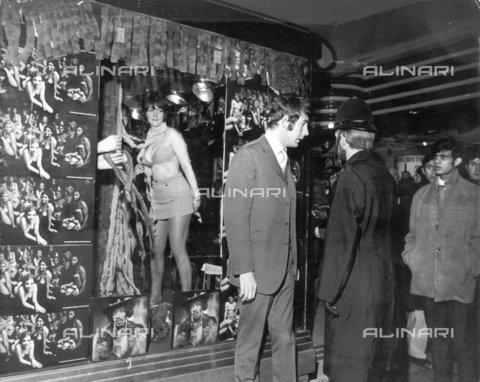 """TOP-F-060652-0000 - John Paul, proprietario di """"I was Lord Kitchener's Valet"""" a Piccadilly Circus, che parla con un poliziotto fuori dal locale mentre 3 modelle in bikini ballano nella finestra per promuovere il nuovo disco di Jimi Hendrix """"Electric Ladyland"""", già in difficoltà per le 21 ragazze nude sulla copertina. La polizia accusò la folla per ostruzione e disse a Paul che sarebbe stato denunciato. 6 Novembre 1968, Generale, """"I was Lord Kitchener's Valet"""" - Data dello scatto: 06/11/1968 - 2005 / TopFoto / Archivi Alinari"""