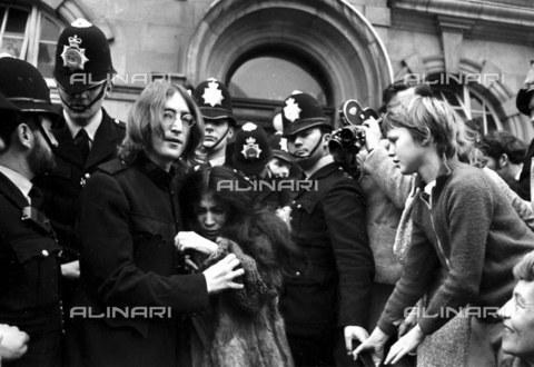 TOP-F-109195-0000 - John Lennon protegge Yoko Ono dalla folla all'uscita dall'udienza al tribunale di Londra per le accuse di possesso di marijhuana e di ostruzione all'attività della polizia. La coppia ottenne la libertà provvisoria su una cauzione di 100 dollari fino al processo il 28 Novembre. London - 19 Ottobre 1968, Pop, John Lennon & Yoko Ono - Data dello scatto: 19/10/1968 - 2005 / TopFoto / Archivi Alinari