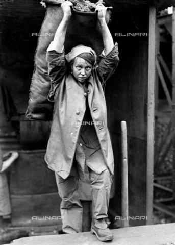 TOP-F-268897-0000 - Nel periodo di guerra 1914-1918, Horace W. Nicholls ha creato una serie di foto documentando i vari  lavori che facevano le donne durante la guerra. Questa foto, scattata ca. 1916 da H. W. Nicholls, mostra una donna mentre porta una sacca di carbon fossile distillato. Officina del gas South Metropole, Old Kent Road, Londra. Guerra, Donna che porta carbon fossile distillato - Data dello scatto: 1916 ca. - 2005 / TopFoto / Archivi Alinari