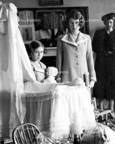 TOP-F-284357-0000 - Le due principesse reali hanno visitato oggi l'Esibizione dei tesori reali al 145 di Piccadilly, Londra. La foto mostra un primo piano della principessa Margaret che accudisce una bambola, vicino alla culla in cui aveva dormito lei stessa quando era più piccola. 28 luglio 1939. Reali, Elisabetta & Margaret - Data dello scatto: 28/07/1939 - 2005 / TopFoto / Archivi Alinari