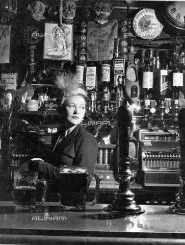 TOP-F-423168-0000 - Alla spina della birra con un cappello di velluto spuntato con un'egretta. 1950. Generale, Alla spina della birra - Data dello scatto: 1950 - 2005 / TopFoto / Archivi Alinari