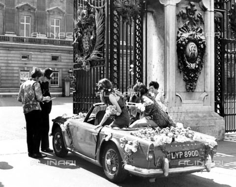 TOP-F-451474-0000 - La regina è stata invitata al Love-in internazionale all'Alexander Palace da parte di alcuni hippie: un ragazzo e due ragazze in minigonna. Sono arrivati davanti al cancello di Buckingham Palace nella loro automobile psichedelica coperta di fiori e hanno mostrato l'invito al poliziotto. Un attimo dopo hanno consegnato l'invito al palazzo, lasciando anche un simbolo tipico degli hippie, un fiore, al poliziotto. Buckingham Palace. 14 luglio 1967. Generale, Hippie - Data dello scatto: 14/07/1967 - 2005 / TopFoto / Archivi Alinari