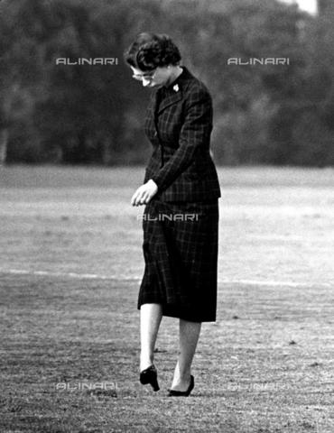TOP-F-463904-0000 - La regina mentre pesta zolle di terra. Sua Maestà la Regina si unisce agli spettatori a pestare i buchi sul campo dopo la partita di polo della Household Brigade durante il torneo di Ascot sul Smiths Lawn, nel Grande Parco di Windsor. 13 giugno 1955 - Data dello scatto: 13/06/1955 - TopFoto / Archivi Alinari