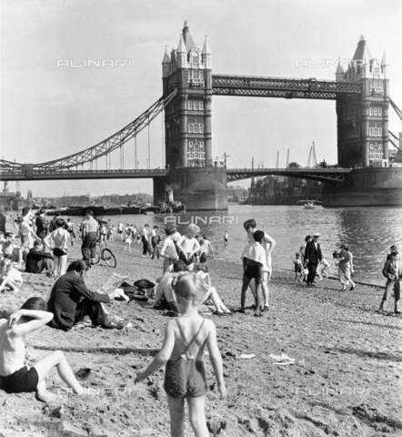 TOP-F-506301-0000 - Spiaggia del Tower, Londra, 1952. Le persone si rilassano sulla spiaggia artificiale del Tamigi, con il Tower Bridge sullo sfondo. Il ponte fu disegnato da Horace Jones. Spiaggia del Tower, Londra, 1952.  Museum of London/HIP - Data dello scatto: 1952 - 2005/HIP / TopFoto / Archivi Alinari
