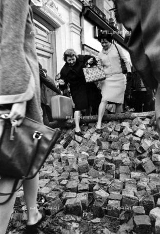 TOP-F-768333-0000 - Sommossa di Parigi, 25 maggio 1968: Parigini che fuggono scavalcando un mucchio di pietre sistemate come una barricata a protezione dei palazzi - Data dello scatto: 25/05/1968 - 2003 / TopFoto / Archivi Alinari