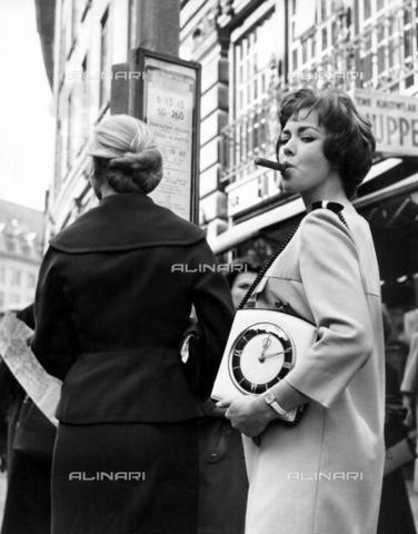 TOP-F-820463-0000 - Beth Rogan alla moda con un sigaro ed una borsa ad orologio. Anni '50. Generale, Donne che fumano - Data dello scatto: 1950 ca. - 2005 / TopFoto / Archivi Alinari