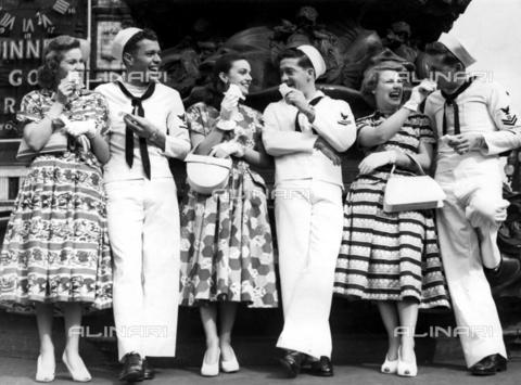 """TOP-F-859227-0000 - Atmosfera primaverile a Leicester Square quando le showgirl di Empire hanno portato i marinai americani (in veste estiva a Londra per la prima volta dal 1933) per un giro turistico a Londra dopo aver visto il film di Sinatra """"On the Town"""". Anni '50. Topografia, Turisti a Londra - Data dello scatto: 1950 ca. - 2005 / TopFoto / Archivi Alinari"""