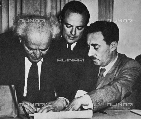 TOP-S-000105-6193 - Ben Gurion mentre firma la Dichiarazione d'Indipendenza (a sinistra). Vicino a lui il ministro degli esteri, Moshe Sharett, che aveva guidato la delegazione palestinese presso le Nazioni Unite diventato in seguito primo ministro - Data dello scatto: 14 Maggio 1948 - TopFoto / Archivi Alinari