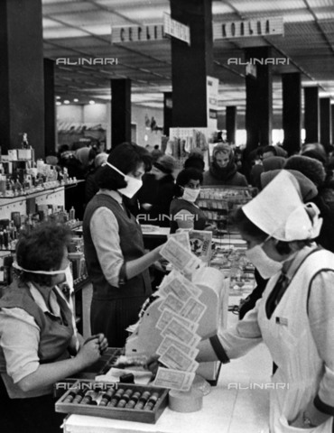 TOP-S-000147-6563 - Due to the threat of an Asian flu epidemic, an order from one of the largest department stores in Moscow, the Mosva Mosva in the Leninsky Prospekt, wears a white gauze mask while serving customers. - Data dello scatto: 30/01/1965 - TopFoto / Alinari Archives