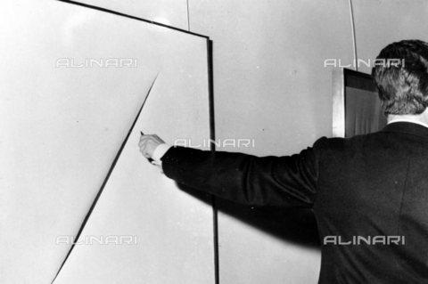 TOP-S-0IPU47-6490 - L'artista Lucio Fontana (1899-1968) taglia una tela, Roma - Data dello scatto: 08/05/1964 - TopFoto / Archivi Alinari