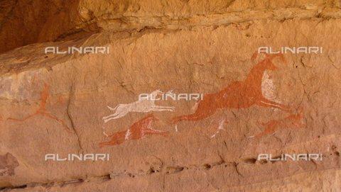 TOP-S-0WF118-1438 - Pittura rupestre raffigurante un cacciatore con cani che inseguono una capra o un'antilope, Periodo preistorico, Libia - Werner Forman Archive/Euan Wingfield / TopFoto / Archivi Alinari