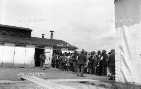 UAQ-S-001002-2003 - Campo di internamento di Katzenau, periferia di Linz, Austria: prigionieri in fila per il rancio - Data dello scatto: 1915-1918 - Archivi Alinari, Firenze