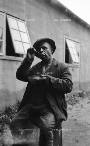 UAQ-S-001002-5001 - Campo di internamento di Katzenau, periferia di Linz, Austria: un prigioniero durante il pasto - Data dello scatto: 1915-1918 - Archivi Alinari, Firenze