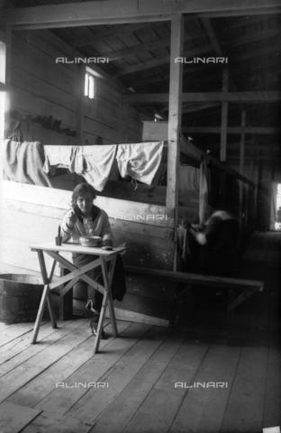 UAQ-S-001002-5009 - Campo di internamento di Katzenau, periferia di Linz, Austria: una donna all'interno della baracca - Data dello scatto: 1915-1918 - Archivi Alinari, Firenze