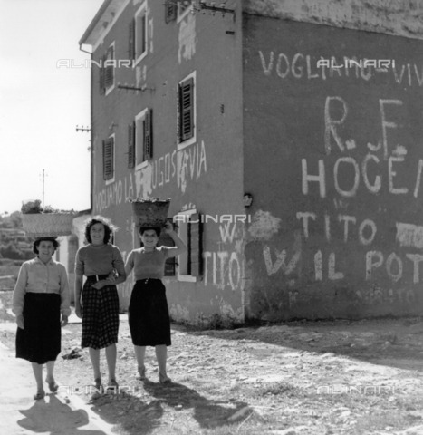 "ULL-F-031920-0000 - Three women photographed in front of a house in ""Zone B"" of ex-Yugoslavia. On the wall of the house written in favor of Yugoslavia - Data dello scatto: 1958 - Claude Jacoby / Ullstein Bild / Alinari Archives"