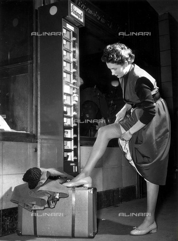 ULL-F-073350-0000 - Automatic nylons distributor to the Zoologischer Garten railway station in Berlin: a woman you try a pair of stockings leaning on a suitcase - Data dello scatto: 1953 - Ullstein Bild / Alinari Archives