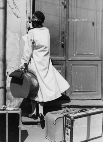 ULL-F-082549-0000 - Woman with luggage rings the doorbell of a door - Data dello scatto: 1933 - Wolff & Tritschler / Ullstein Bild / Alinari Archives