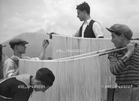 ULL-F-185133-0000 - Dough preparation in Campania: group of kids hang noodles on a bamboo stick to dry - Data dello scatto: 1932 - Alfred Eisenstaedt / Ullstein Bild / Alinari Archives
