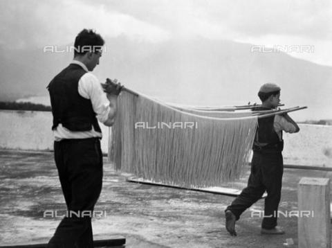 ULL-F-185377-0000 - Dough preparation in Campania: transport of spaghetti on a bamboo stick to dry - Data dello scatto: 1932 - Alfred Eisenstaedt / Ullstein Bild / Alinari Archives