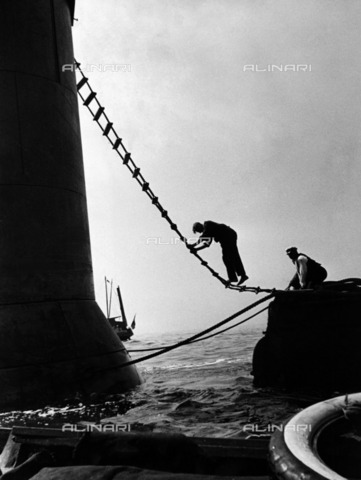 ULL-F-236443-0000 - Trying to save the French frigate HMS Lutine: sailors who try to reach the ship's tower through a rope ladder - Data dello scatto: 1933 - Alfred Eisenstaedt / Ullstein Bild / Alinari Archives