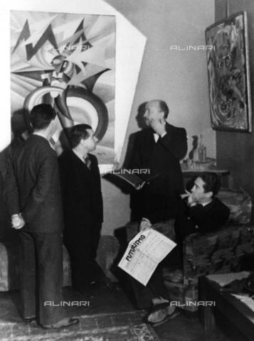 """ULL-F-264326-0000 - Meeting with the editorial staff of the periodical 'Futurism': Mino Somenzi (1899 -1948), Filippo Tommaso Marinetti (1876-1944), Enrico Prampolini (1894-1956) and Bruno Giordano Sanzin (1906-1994). In the background the painting """"Marinetti temporale patriico, Ritratto psicologico"""" (1924) by Fortunato Depero (1892-1960) - Data dello scatto: 1933 - Felix H. Man / Ullstein Bild / Alinari Archives"""