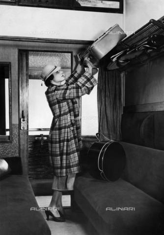 ULL-F-326506-0000 - Woman luggage system in the luggage rack inside the car of a train - Data dello scatto: 1935 - Malina / Ullstein Bild / Alinari Archives
