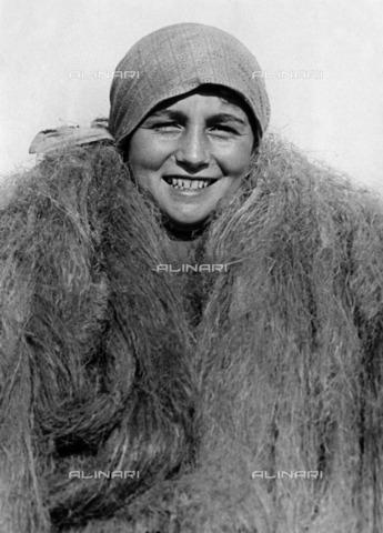 ULL-S-000101-4246 - A young peasant wraps the neck of hemp fiber; Image published on Berliner Illustrirte Zeitung - Data dello scatto: 06/1919 - Ullstein Bild / Alinari Archives