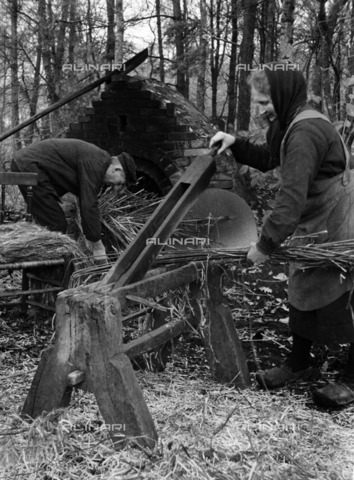 ULL-S-000107-7763 - Two peasants cut hemp fiber and dry them in a stone oven; Published in Das Blatt der Hausfrau - Data dello scatto: 07/1936 - Saebens-Worpswede / Ullstein Bild / Alinari Archives